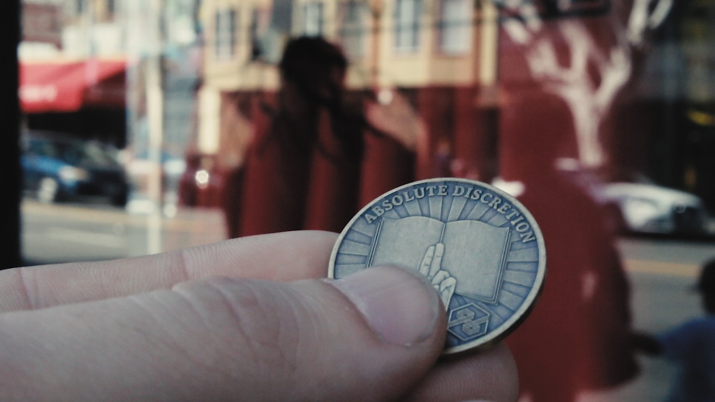An extreme close up of a hand holding a unique coin. The background of a city street is blurred. The coin features an open book, a hand holding two fingers up and the words 'Absolute Discretion' across the curved edge.
