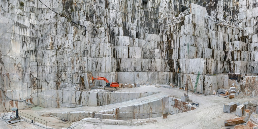 An orange digger stands out in amongst white stone, almost looks like marble. This is clearly a man-made construction site with ramps and railing carved out for access for machinery.