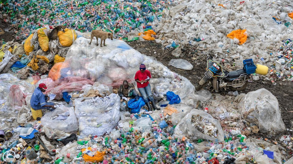 3 Black Men sit amongst a plastic landfill. They are resting on piles of plastic bags surrounded by bottles. A dog looks down from one of the plastic mountains.