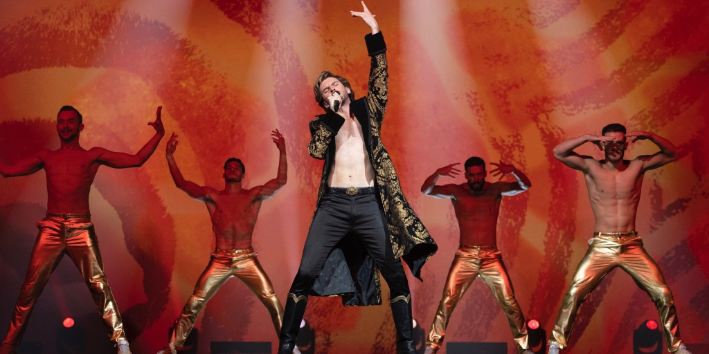 A still from 'Eurovision Song Contest: The Story of Fire Saga'. Alexander (Dan Stevens) is on stage performing 'Lion of Love' against a red backdrop at the Eurovision Song Contest. He is posing with his legs spread open, holding a microphone to his face and raising his other arm up high. Alexander has blonde hair, and is wearing tight black trousers and a black and gold robe over his bear torso. Behind him there are four topless male dancers wearing tight gold trousers.