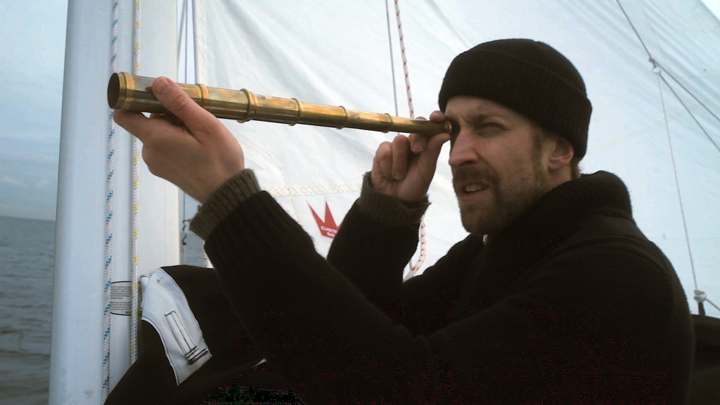 A young bearded man is stood aboard a ship. He is wearing a black jumper and black woolly hat. He is looking through a collapsible telescope at something out of shot.