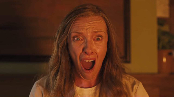 Toni Colette as Annie in Hereditary (2018). Annie faces the camera, her mouth open in terror.