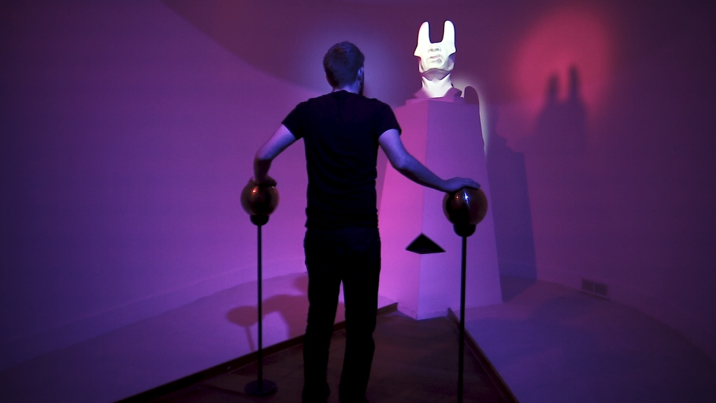 A man wearing all black stands in a room lit with purple. He is facing away from the camera with his hands on two metal balls fixed to the ground by poles. He is looking up at a white bust sculpture of a distorted head,