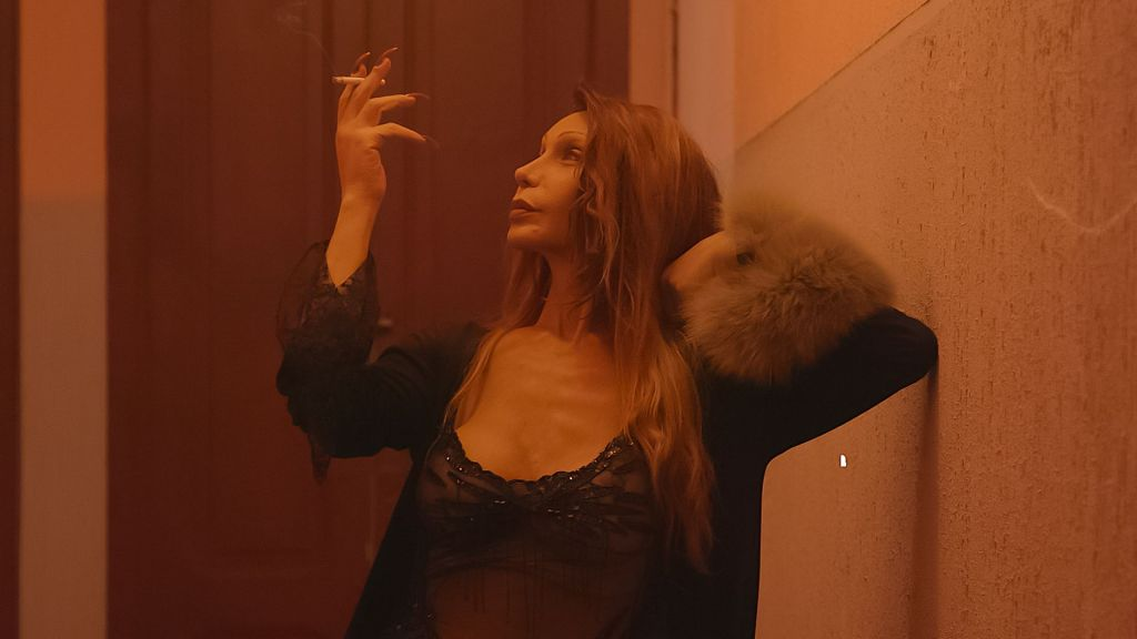 A transgender sex worker, Luana Muniz, stands in the pink-tinted corridor of her hostel. She is incredibly glamorous wearing black lingerie. She is raising her hand holding a cigarette.