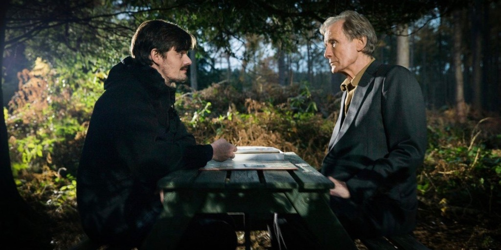 A 70 year old man (Bill Nighy) sits at a picnic table in a forest. He is wearing a grey suit jacket and mustard shirt. He is sitting across from his son, in his 30s (Sam Reid). His son has shaggy hair and a moustache, he is smirking as he stares at his father.