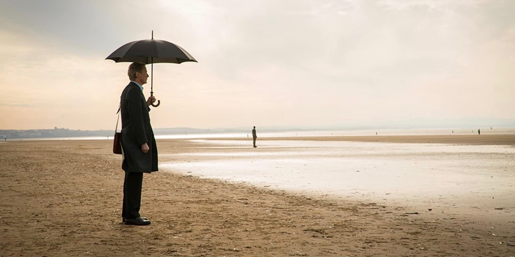 A man in his 70s stands on a sparse beach in office wear. He carries a satchel and holds his umbrella above his head, it is raining.