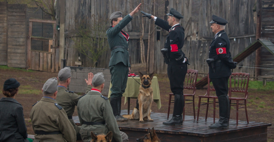 Two Nazi SS Officers stand on a podium. One is giving the Nazi salute to another office on the podium who is receiving a medal. He has a young German Shepard on a lead with him. Four other Nazis are watching the ceremony.