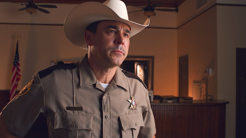 A concerned Texas Sheriff wearing a Stetson looks at someone out of frame