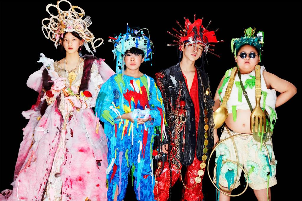 Four Japanese teenagers, 1 girl and 3 boys are stood in a line. They are wearing elaborate stage costumes that look very homemade in bright colours. Each is wearing a crazy headpiece constructed from found objects.
