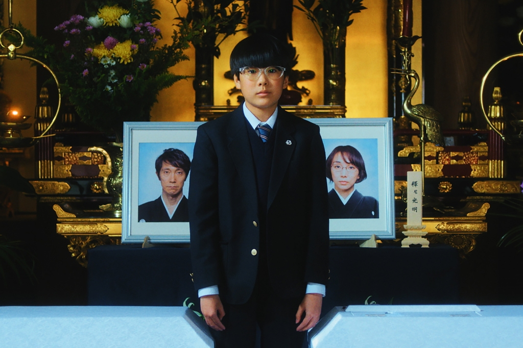 A young Japanese boy, around 13 years old stands in a black suit in front of a memorial to his deceased parents. Their photos are behind him on an elaborate gold altar.