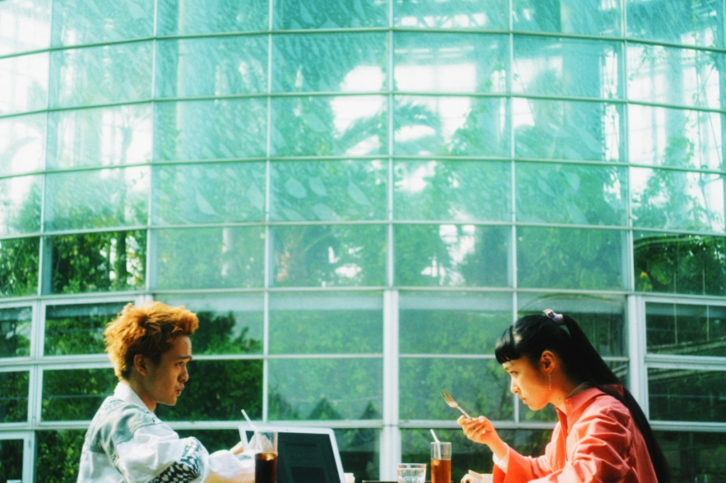 Two Japanese teenagers, a boy with dyed ginger hair and a girl with a long, sleek ponytail, are eating lunch together.  We can only see their head and their shoulder are the rest of the frame is filled with trees and glass, the pair look to be sat by a conservatory.