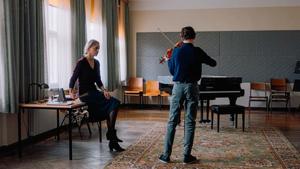 Nina Hoss leaning/seating on a table, as she instructs her pupil as he plays the violin. His back facing the camera.