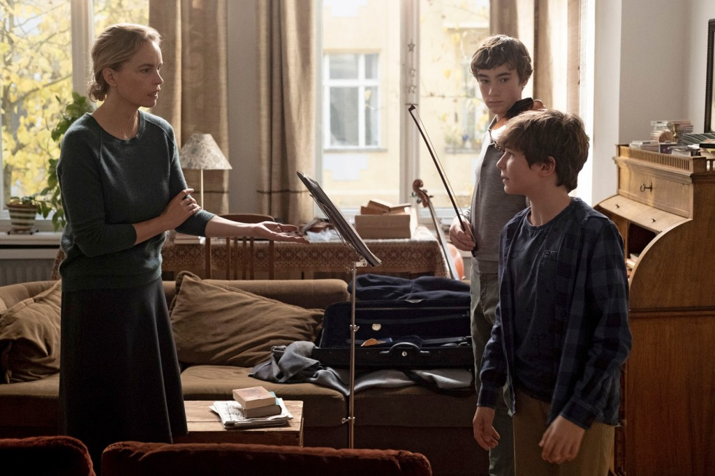 Nina Hoss (left) facing her pupil and her son as she angrily instructs them in a violin lesson.