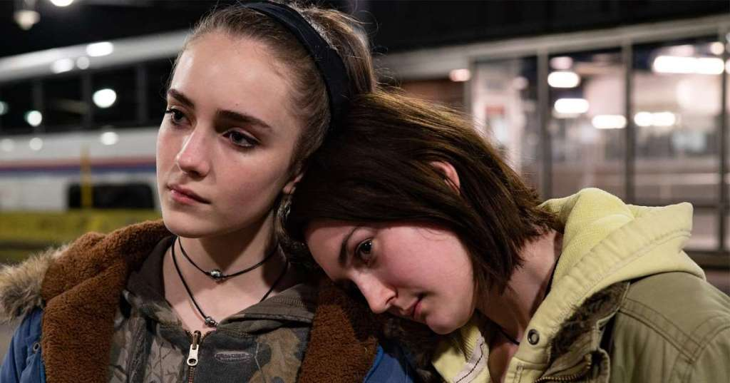 Still from Never Rarely Sometimes Always (2020). A solemn close up of two girls, Autumn leans her head on her cousin Skylar's shoulder, who gazes into the distance.
