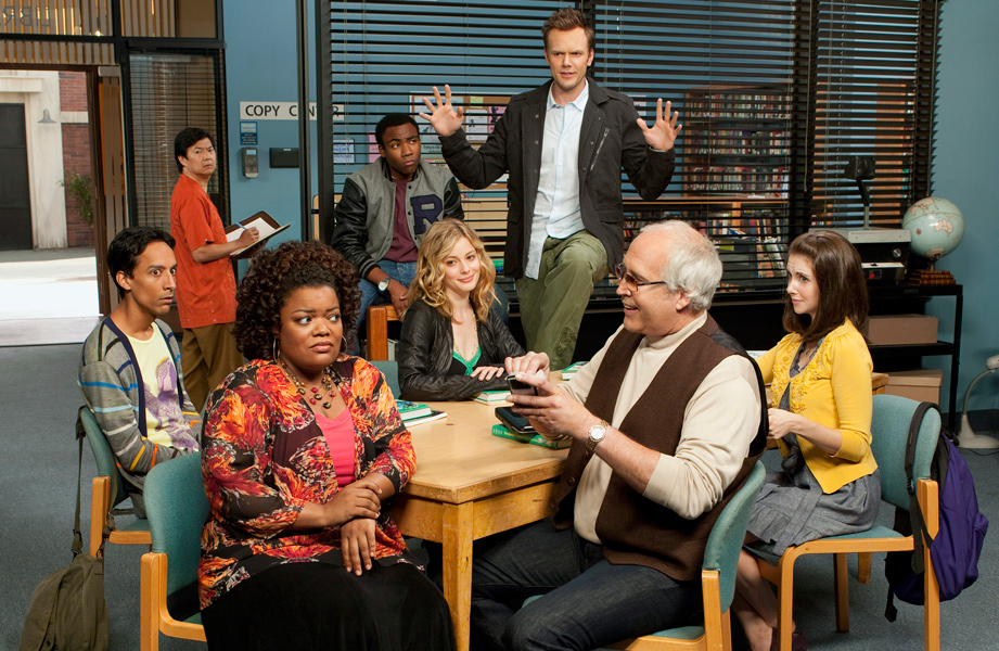 A promotional image from NBC's sit-com 'Community'. A group of 8 individuals sit inside a college library.   Left to Right: Abed (Danny Pudi) a 20-something Palestinian-Polish man wearing a striped cardigan looks shocked towards Shirley (Yvette Nicole Brown) an African American 40 year old woman wearing bright floral prints. In the background Senor Chang (Ken Jeong), a 30-something year old Koren-American looks towards Shirley in shock. Troy Barnes (Donald Glover) can be seen also in the background. He is a 20-something African American man wearing a Varsity jacket. Troy is looking towards, Jeff (Joel McHale) a 30 something man and central character of this image. Jeff is standing up with his hands raised giving a grand speech. His love interest Britta (Gillian Jacobs) is sitting below him. She has blonde hair and is paying Jeff no attention, instead looking towards Shirley. Off to the right hand side of the image we see Annie (Alison Brie), a 20-something women with long dark hair and a yellow cardigan. She is raising an eyebrow towards the final character, Pierce (Chevy Chase), a much older gentleman with grey, balding hair and dark glasses. He is wearing a waistcoat and holding a mobile phone, clearly irritating Shirley who is the recipient of his conversation.