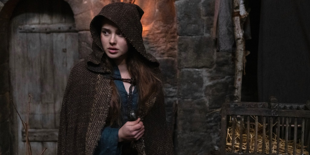 Nimue (Katherine Langford) cloaked in a hessian cape and holding the hilt of the Sword of Power. She is looking suspiciously to her right and is standing in what looks like a castle's keep.