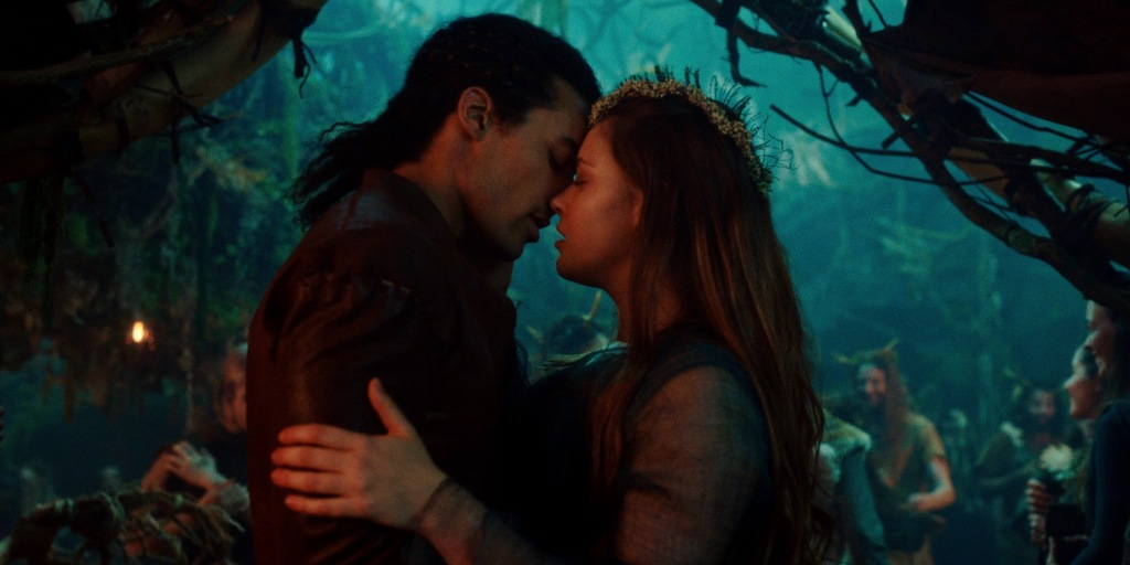 (L to R) Devon Terrell and Katherine Langford embracing and about to kiss. There is a busy crowd of other mythical looking folk looking on.