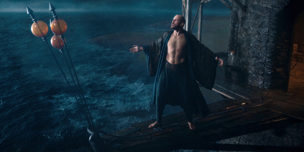 Gustaf Skarsgård standing on a plank, which overlooks rough waters. He is poised as though he is shouting at the sky.
