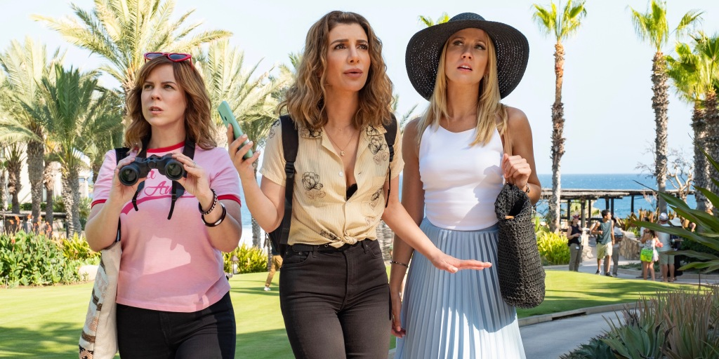 Kaylie (Sarah Burns), Wesley (Nasim Pedrad) and Brooke (Anna Camp) are three best friends. They are walking together on what looks like a holiday resort. Kaylie is the shortest of the group, with shoulder length curled light brown hair with love heart sunglasses perched atop her head. She is wearing a pink tshirt and jeans, carrying a tote bag over her shoulder and also carrying binoculars. Wesley is the tallest of the group with beachy blonde wavy hair she has black jeans on with a yellow floral shirt and has a backpack on her back. She has her phone in her hand, the girls are clearly trying to find something. Brooke is stood on the end looking perplexed, she looks ready for a holiday. Black sun hat, white vest top and long blue skirt with a beach bag over her shoulder.