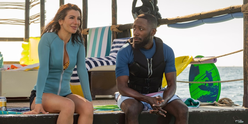 Wesley (Nasim Pedrad) is sat out at a beach hut with Sean (Lamorne Morris). Wesley is looking out into the distance. Her hair is wet and she is wearing a blue scuba top with a leopard print bikini underneath. Sean is a Black man with very short hair and a neatly kept beard. He is rather muscular and is wearing a blue t-shirt with a black lifejacket over the top. He is looking towards Wesley.