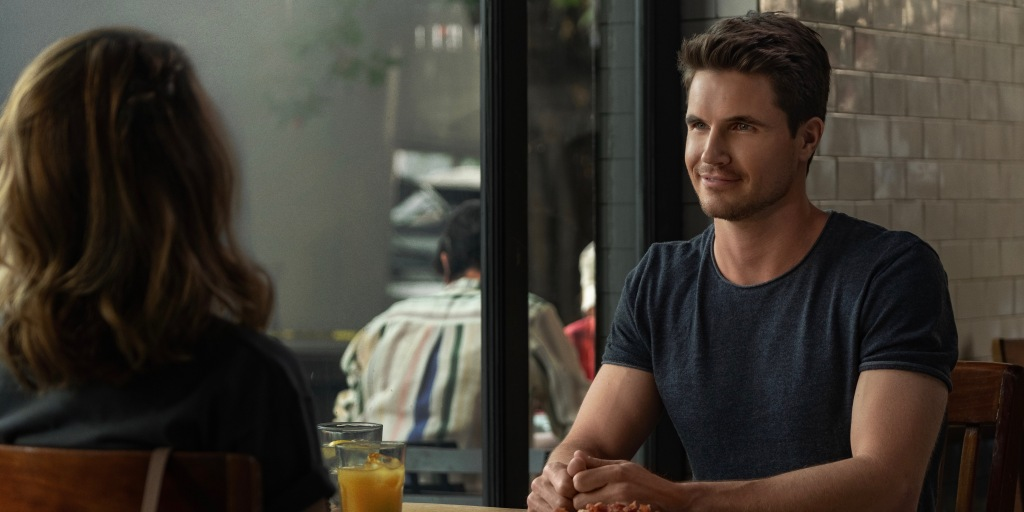 Wesley (Nasim Pedrad) sits across a restaurant table from Jared (Robbie Amell). The focus is on him and Wesley has her back to the camera. Jared is your typical all-American guy, quiffed hair, plain t-shirt, dark eyes and bushy eyebrows.