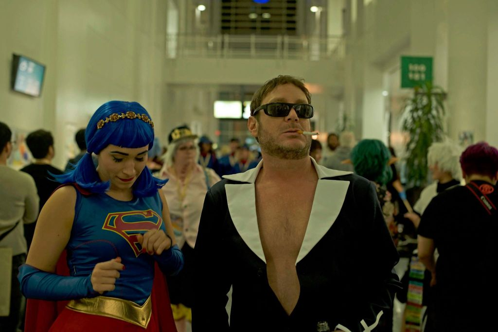 Lana (Margot Graff) is at a comic convention dressed as Supergirl in a cutesy blue spandex dress with a blue wig in bunches and a gold headband. She is standing next to Jeff (Jeff Nimoy). He looks washed up, scruffy, wearing sunglasses with a cigarette hanging out of his mouth and an open blazer that reveals he is shirtless underneath.