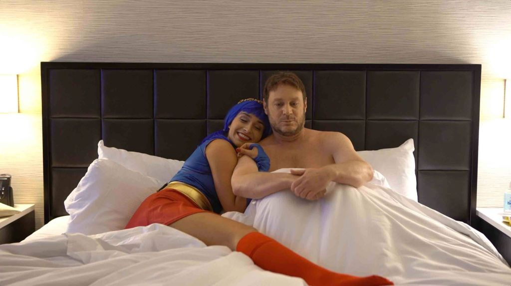 Lana (Margot Graff) and Jeff (Jeff Nimoy) are in a big white hotel bed together with a black leather quilted headboard. Jeff is in the white sheets cradling his knees to his chest as Lana, still wearing her Supergirl costume, snuggles into him with glee.