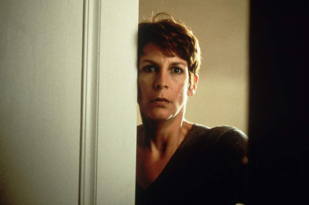 Laurie Strode (Jamie Lee Curtis) is shown in close-up here in a still from Halloween H20. She has short, dark cropped hair and a V-neck jumper on, she is partially hiding behind a door frame, looking in fear towards the camera.