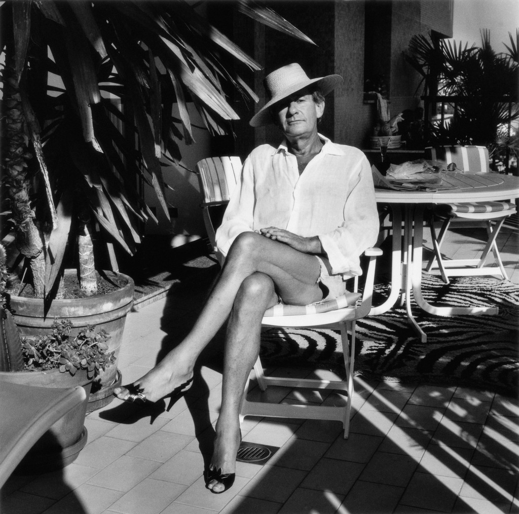 A portrait of Helmut Newton sitting in a garden surrounded by plants. The image is in black and white, Helmut is in around his 50s here, wearing short denim shorts, an open white shirt, angled straw hat and high black heels. He is posing like a woman sat on a chair.