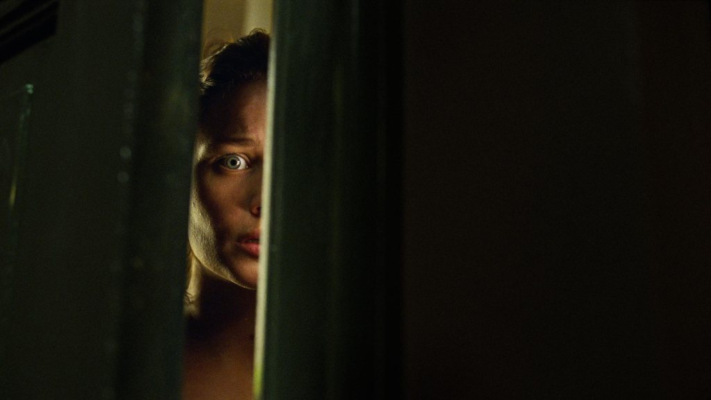 A still from 'Lake of Death'. Lillian (Iben Akerlie) is looking through a crack in a door, terrified. the image is shrouded in black so all you can see is her scared face in the doorway.
