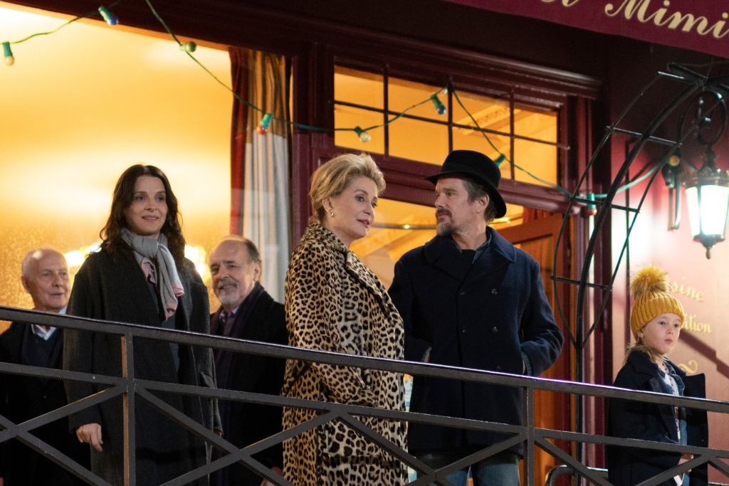 Lumir (Juliette Binoche) stands on a balcony with her mother Fabienne (Catherine Deneuve), husband Hank (Ethan Hawke) and young daughter Charlotte (Clementine Grenier). They are all wrapped up in hefty, dark winter coats except from Fabienne, whose leopard print fur coat stands out in the image as the most glamorous lady of the group, with coiffed short blonde hair and a beautifully made-up face.