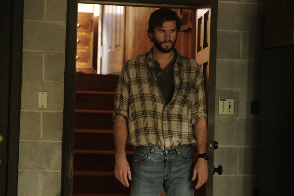 Kyle (Liam Hemsworth) stands in a doorway of a bare, breezeblock built room. His brow is furrowed with a deep look of concern on his face. He wears a checked shirt in neutral tones with a grey tshirt underneath, tucked into a pair of light blue jeans.