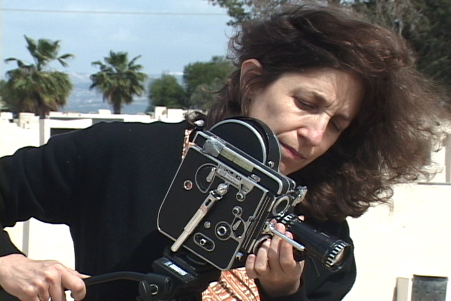 An old image of filmmaker Lynne Sachs. She is wearing all black and has dark hair that is blowing in the wind. She is fiddling with the lens of a beautiful black and silver  film camera.