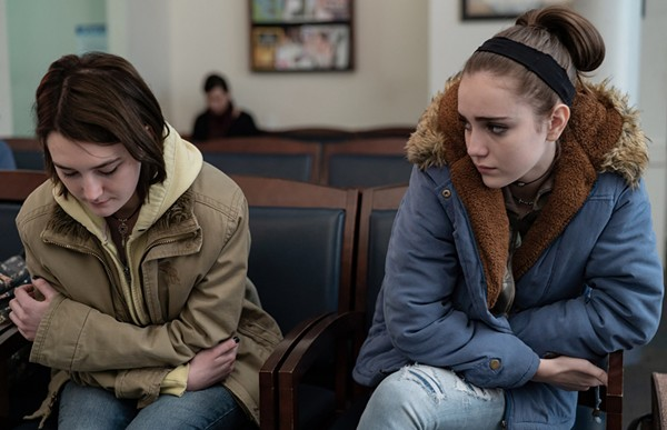Sidney Flanigan and Talia Ryder in Never Rarely Sometimes Always (2020). Autumn and Skylar sit side by side in a doctor's waiting room. Autumn is looking down at her knees, arms wrapped around her body. Skylar watches her with a look of concern.