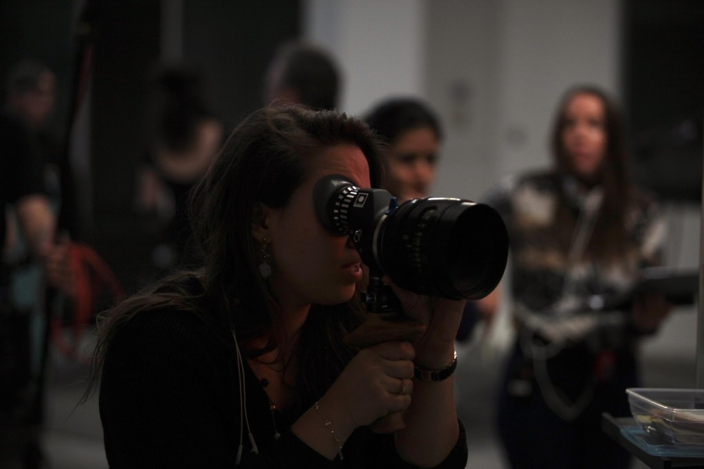 Director Nour Wazzi is looking down the large lens of a camera, planning out her next shot. A crew of people can be seen blurred behind her.