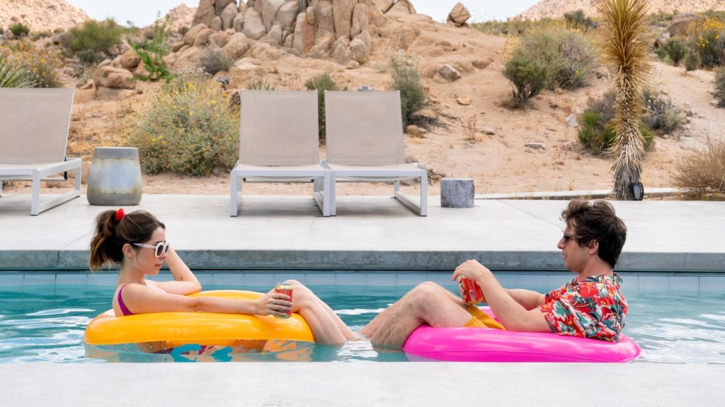 Sarah (Cristin Milotti) and Nyles (Andy Samberg) float on rubber rings in a desert hotel pool. There is no one around them, just empty chairs by the poolside. Sarah wears a pink bathing suit with her hair pulled back into a ponytail and big white sunglasses and a can of soda in her hand. Nyles is sat in a pink rubber ring and wears a red Hawaiian shirt. His brown hair is tousled and messy. He also holds a can of soda.