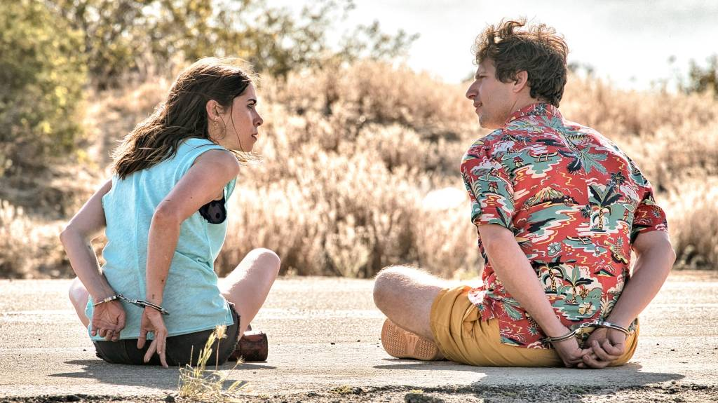 Sarah (Cristin Milotti) and Nyles (Andy Samberg), both around aged 30, sit with their backs to the camera. They are both handcuffed. Sarah, wearing a blue tank top and cutoff denim shorts and long brown hair, is looking at Nyles with anger. Nyles is wearing yellow shorts and a red Hawaiian patterned shirt. His brown hair is blowing in the wind. It appears they are sat in the desert, the landscape behind them has sandy coloured bushes but looks empty.