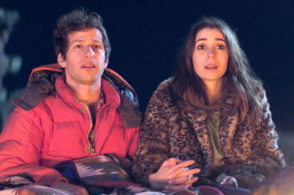Nyles (Andy Samberg) sits with  Sarah (Cristin Milotti) by an unseen campfire. The pair are sitting holding hands, cosied up underneath a blanket and big jackets, Nyles is a red padded jacket and Sarah's is a leopard print fur coat. The pair are a 30-something young white couple who look very similar, they are well suited to each other, both with dark brown wavy hair. They are pulling the same surprised expression.