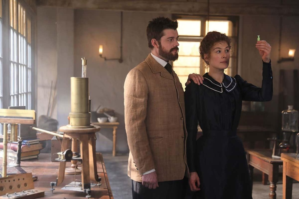 A still from the film 'Radioactive'. Pierre (Sam Riley) stands with wife Marie Curie in her laboratory. He is wearing an late 19th century tan suit and has short dark hair and a thick moustache and beard. His hand is on Marie's shoulder as she looks towards a small vial she is holding up and examining.