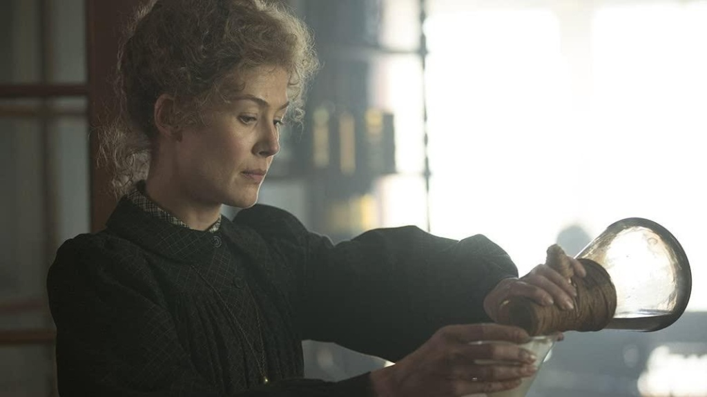 A still from the film 'Radioactive'. Marie Curie (Rosamund Pike) is wearing a black, late 19th century dress with a small peter pan collar. Her blonde, frizly hair is pinned high up on her head. She is doing some form of experiment, pouring a liquid from a scientific beaker into another container.