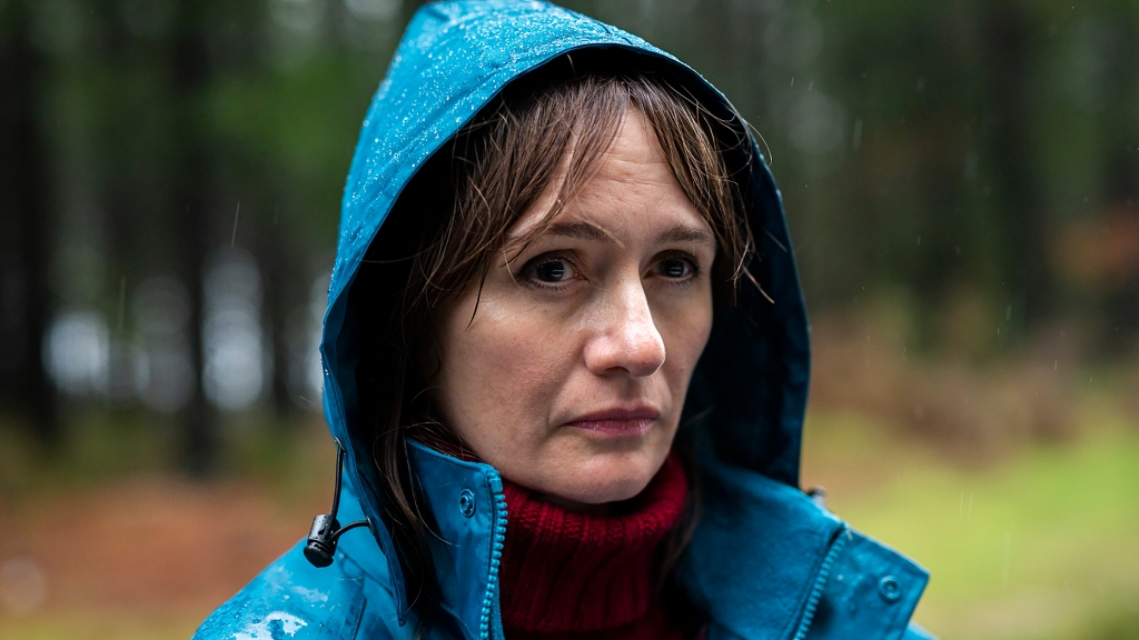 Kay (Emily Mortimer), a 40 something woman stands in the rain in her blue raincoat. The shot is a close up of her face looking into the distance. Her dark hair is wet and a red turtleneck jumper is pulled up close to her chin.