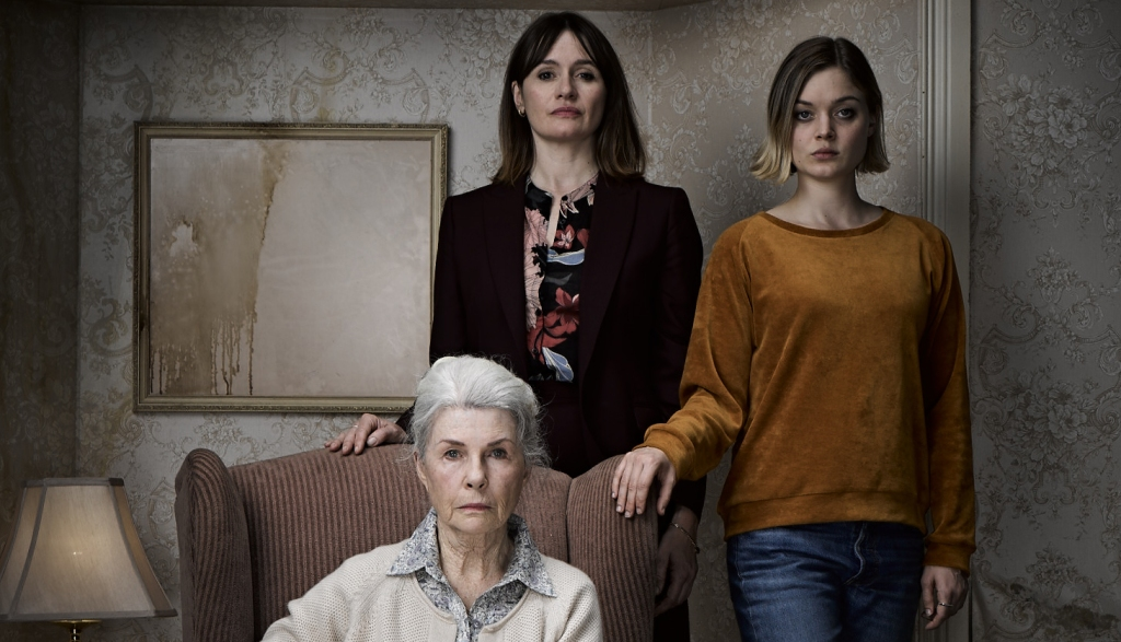 3 generations of women are in a drab, gray living room. It is as thought they are being photographed for a family portrait. The grandmother Edna (Robyn Nevin) sits on a grand armchair, her silver hair framing an incredibly stern look upon her face. Standing behind the chair is 40 something daughter of Edna, Kay (Emily Mortimer). She is pale and slim, with office wear and dark hair. She also looks displeased to be in the picture. Her 20 something daughter Sam (Bella Heathcote) flanks the family on the fight, her hand on her grandmother's chair. She is wearing an orange sweatshirt and has a short, blonde-tipped bob and a vacant expression.