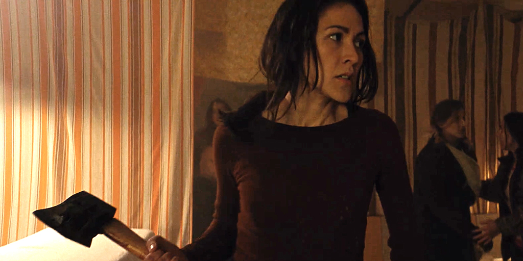 Elle-Máijá Tailfeathers in the film 'Blood Quantum'. She is in motion, holding an axe, looking like she is about to swing. She is an Indigenous woman, around her 30s with dark hair that is tied up and a sharp jawline. She wears a plain burgundy long sleeve top.