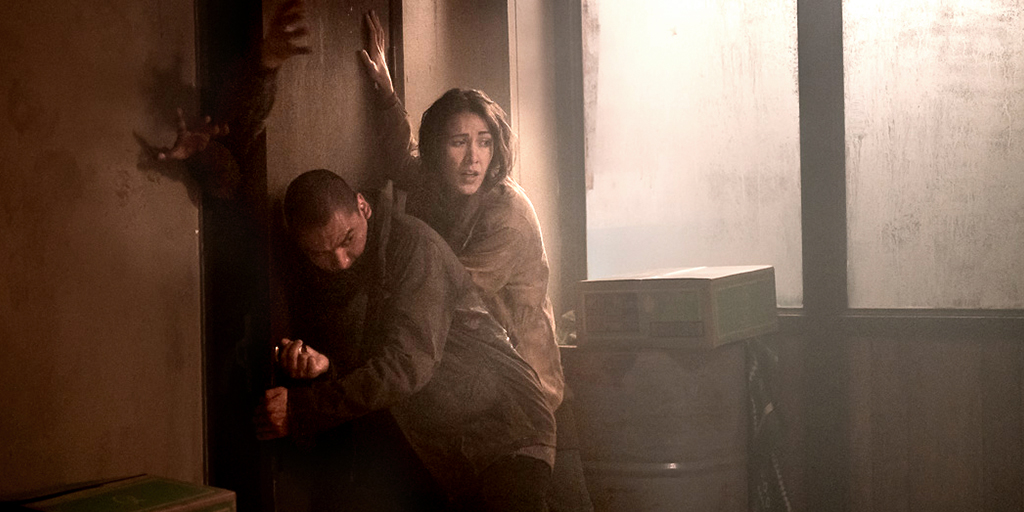 Indigenous actors Forrest Goodluck and Elle-Máijá Tailfeathers in 'Blood Quantum'. The pair are pushing against a large door that zombie hands are grabbing through. Forrest has a shaved head and a khaki jacket, he is throwing most of his weight against the door. Elle-Máijá has long dark hair and a tan jacket, she is pressing on the door much lighter and is looking behind her.