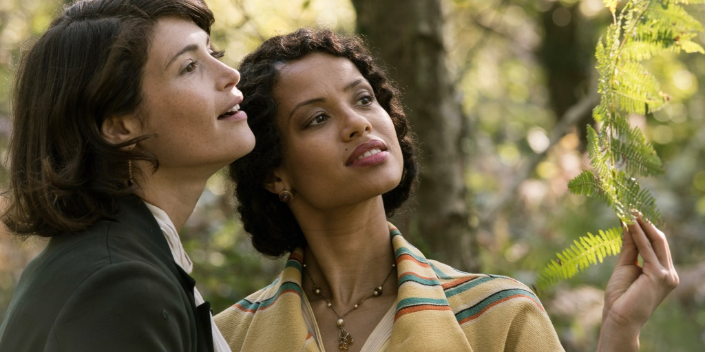 A still from 'Summerland'. (L to R) Alice (Gemma Arterton) and Vera (Gugu Mbatha-Raw) are close together and examining leaves. Alice has short brown hair and is wearing a dark green coat. Vera has curly short brown hair and is wearing red lipstick, small golden earrings, a gold necklace with pearls, and a striped yellow coat. Pictured from the shoulder up.