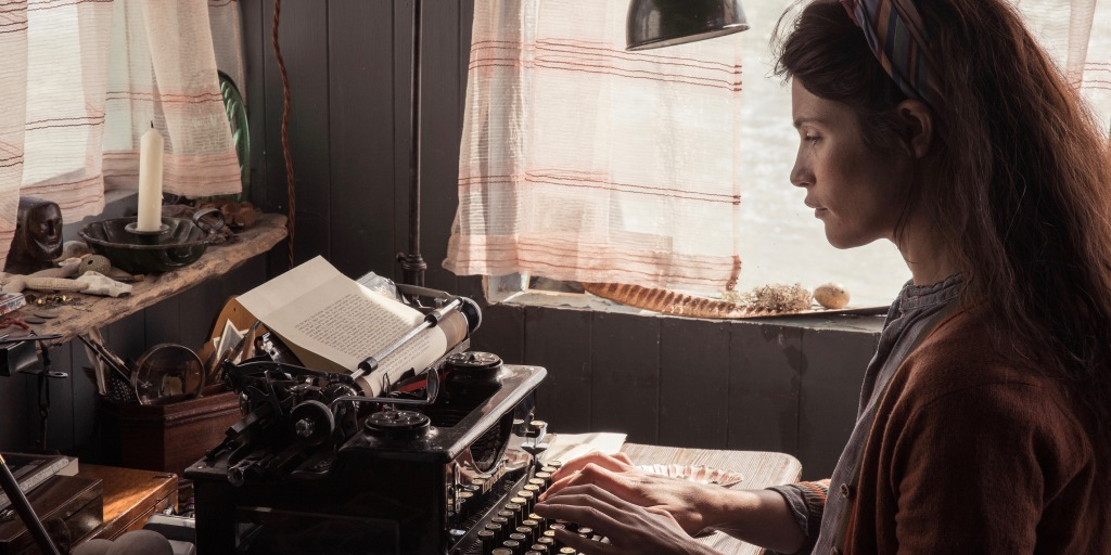 A still from 'Summerland'. Alice (Gemma Arterton) is seated at a desk typing on an old typewriter that is surrounded by small objects and a candle. She has unkempt long brown hair and is wearing a striped hairband, a grey shirt and brown cardigan.