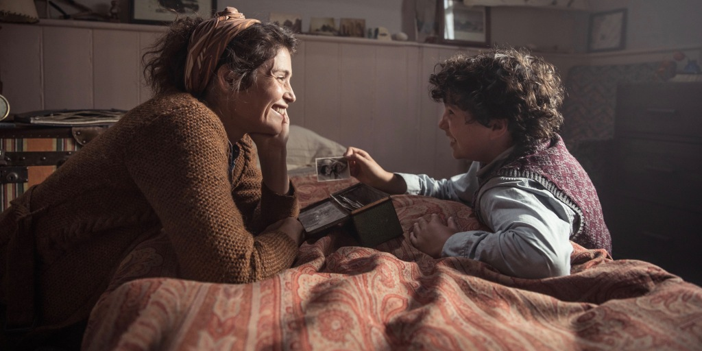A still from 'Summerland'. (L to R) Alice (Gemma Arterton) and Frank (Lucas Bond) are half laying half kneeling against a twin sized bed. Frank holds a small black and white photograph to show Alice, who smiles at him.