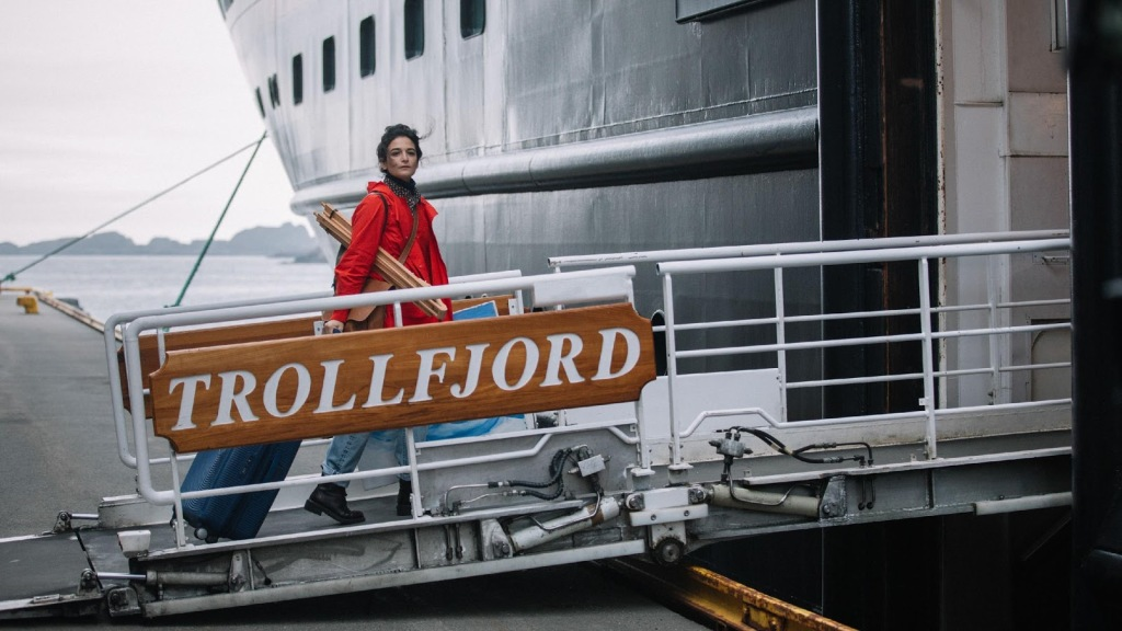 A woman in her late 30s (Jenny Slate) is shown boarding a large ship called the 'Trollfjord'. She is walking along the bridge to the ship wearing a red raincoat and carrying a large brown satchel, her dark her is tied up and messy, she looks into the distance.