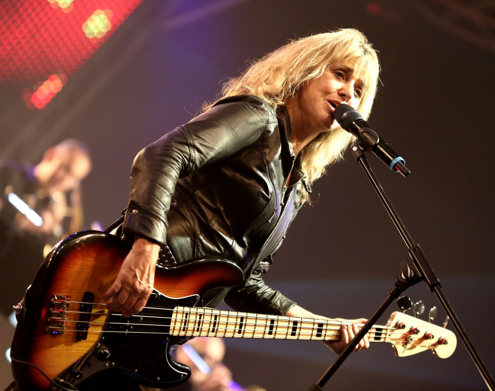 An older Suzi Quatro with grown out blonde hair wearing a leather jacket plays her bass guitar on a stage. This is a photograph from a live performance.