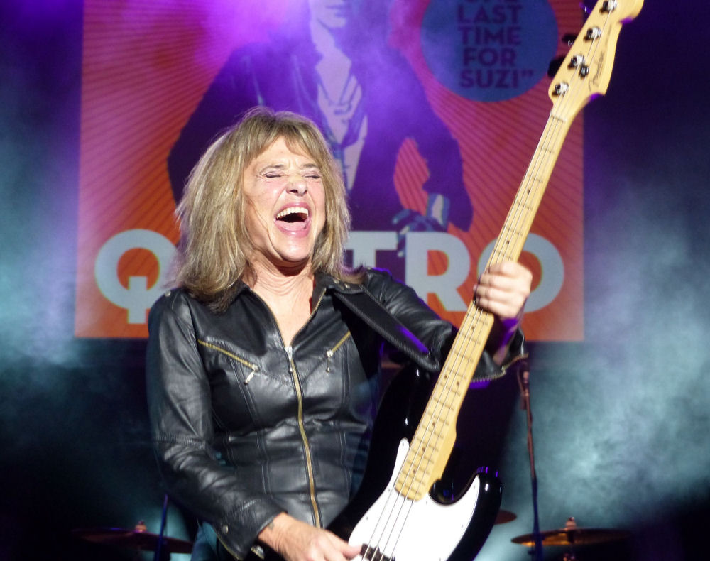 An older Suzi Quatro is pictured her on stage shaking her bass guitar in the air. Her eyes are shut and mouth open in exaltation. She has shoulder length blonde hair and wears a leather jacket. Her bass guitar is black.